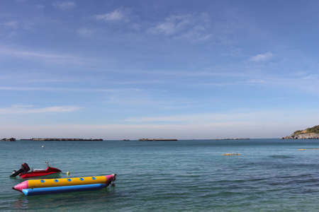 Picture of the view of the sea and sky. There are red scooter boat and yellow banana boat in the foreground. Zdjęcie Seryjne