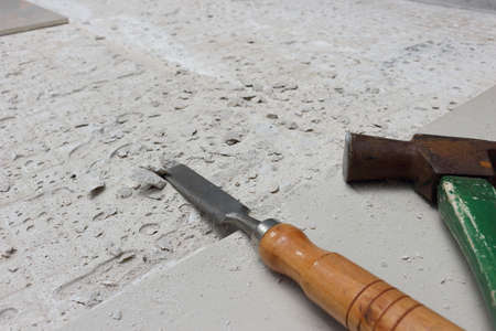 A hammer for hammering nails and a wood chisel is placed beside the area being newly tiled. Imagens