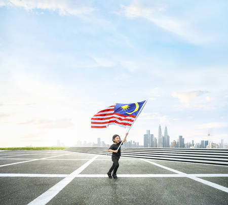 Happy boy running while holding Malaysia flag on open space with Kuala Lumpur cityscape.