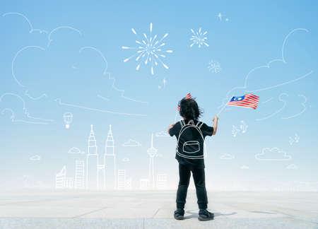 Little boy holding Malaysia flags. Celebrating Malaysia Day.