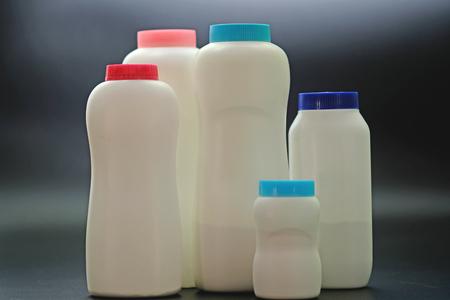 White plastic baby powder bottle isolated on black background Stock Photo