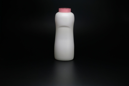 White plastic baby powder bottle isolated on black background Stockfoto