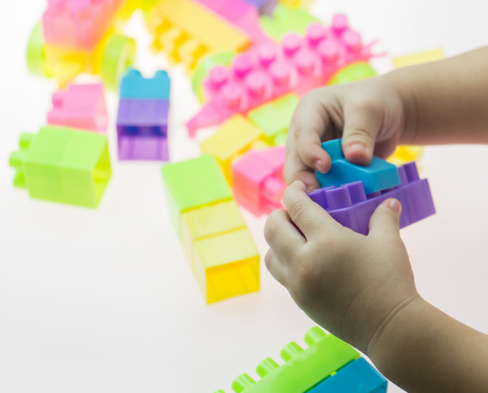 yellow lego block: girl playing blocks on white background