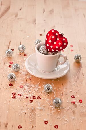 A red glittery heart in a cup and glittery balls