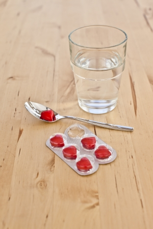 lovesickness: A glass of water and a blister with red heart shaped pills
