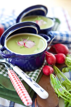 Two little pots with green soup and beets