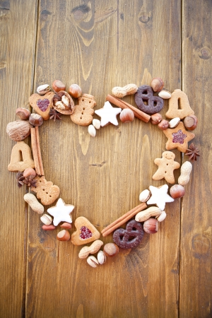 Heart-shaped frame made of cookies and nuts for christmas photo