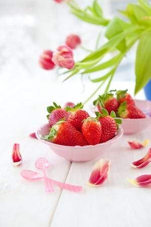 Verse rode aardbeien en roze tulpen Stockfoto