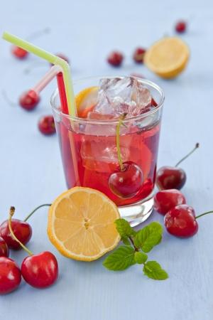 Homemade  lemonade   iced tea with fresh cherries, lemons and mint