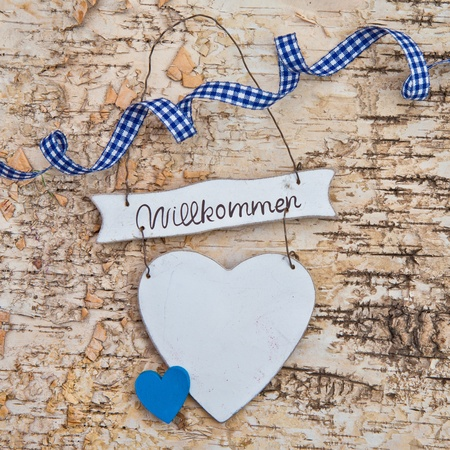 willkommen: Heart with welcome written in german on a wooden background  made of birch