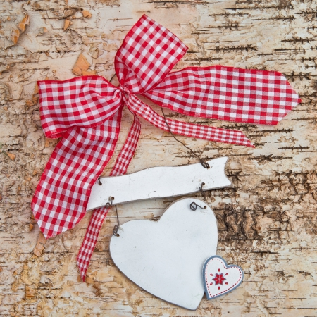 Blank heart on wooden background made from birch with checkered red ribbon photo