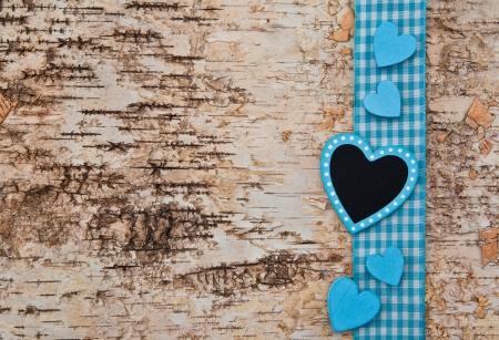 Houten achtergrond met blauw geruit lint en harten