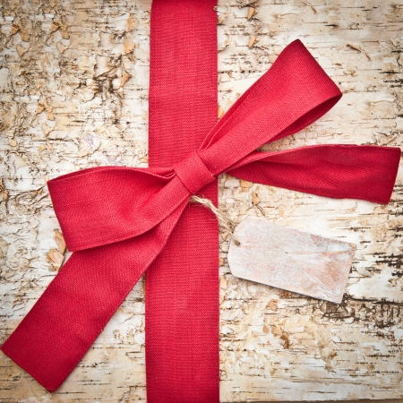 Wooden background made of birch with a big red bow