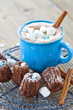Hot chocolate with marshmallows and little chocolate cakes photo