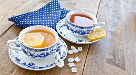 Various teas with fresh lemon in white and blue china cups photo