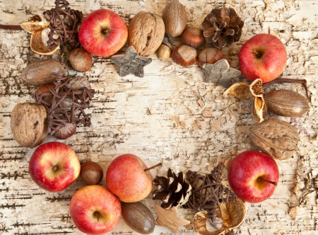 Rustic wooden background with various nuts and apples