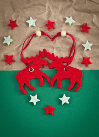 newyears: Red elks made from felt on green paper background Stock Photo