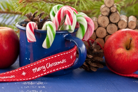 Colroful candy canes in blue tin mug Stock Photo