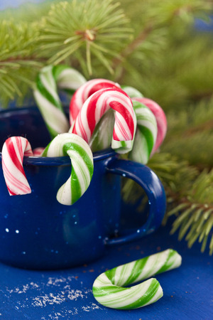 Colorful candy canes in blue tin mug