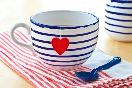 emaille: Big striped mug of tea with a red heart Stock Photo