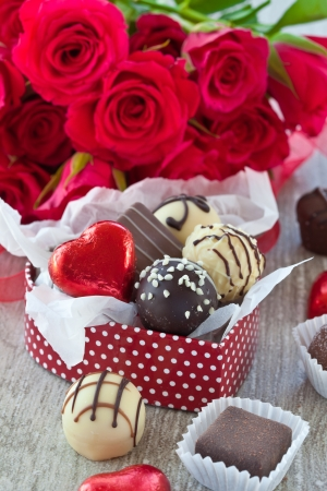 A variety chocolates and truffles on a grey background photo