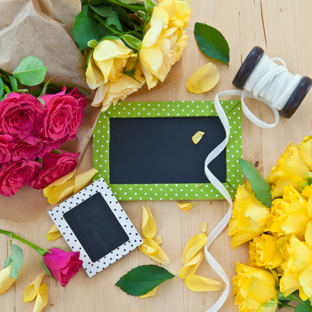Yellow and pink roses and a little blackboard with copy space photo