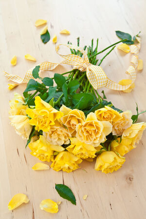 emaille: Fresh yellow roses with a checkered ribbon on wooden table