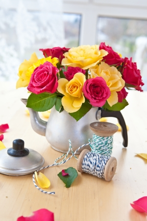 emaille: Yellow and pink roses in a vintage tea can Stock Photo