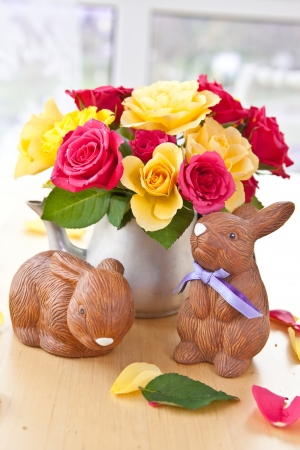 emaille: Yellow and pink roses in a vintage tea can and little easter bunnies Stock Photo
