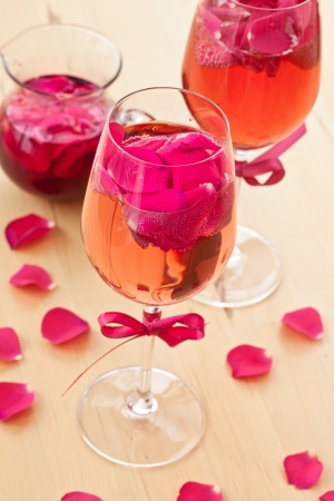 Pink Cocktail with fresh rose petals on wooden table Stock Photo