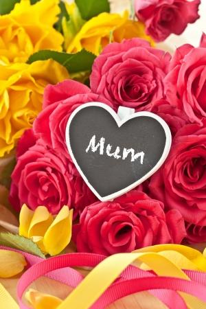 Geel en roze rozen en een beetje bord met kopie ruimte Stockfoto