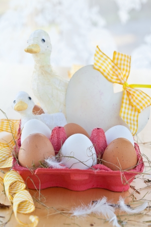 Box of brown and white chicken eggs and easter decorations photo