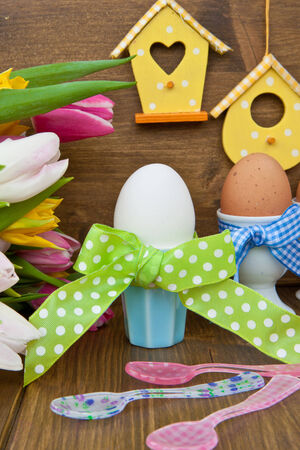 Fresh colorful tulips and boiled eggs in colorful cups for easter Stock Photo - 25276016