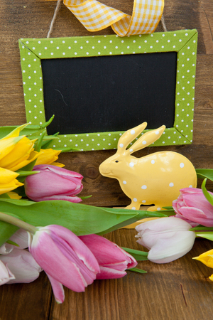 Little dotted easter bunny and colorful tulips in front of a chalkboard photo