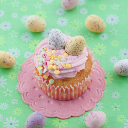 Little cupcake with frosting and colorful easter eggs on green photo