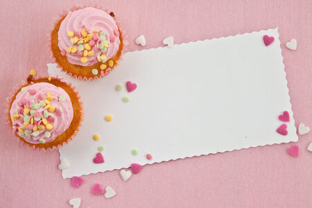 Little cupcake with frosting and colorful sprinkles on pink photo