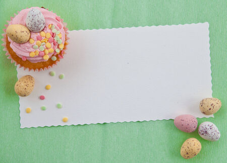 Little cupcake with frosting and colorful easter eggs on pink photo