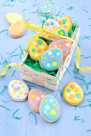 Colorful egg-shaped cookies for easter on blue photo
