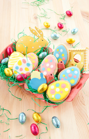 Colorful egg-shaped cookies and chocolate eggs for easter photo