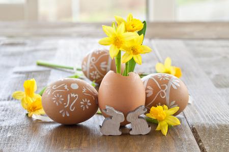 Gele narcissen in eierschaal op een rustieke houten