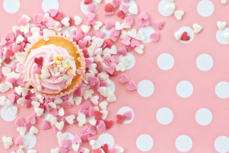 Little cupcake with pink frosting and sprinkles photo
