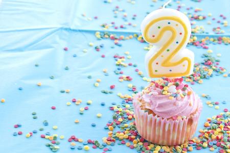 Weinig cupcake met roze glazuur en hagelslag en een 2e verjaardagskaars Stockfoto