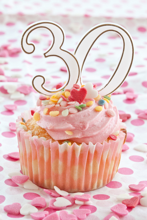 Little cupcake with pink frosting and sprinkles for a 30th birthday photo