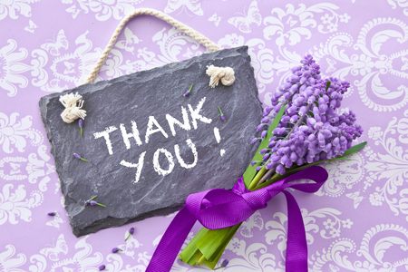 small purple flower: Fresh hyacinths  with ribbon and a slate chalkboard on blue Stock Photo