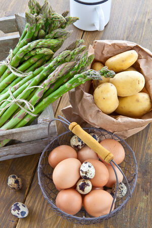 Fresh asparagus, potatoes, and raw eggs in wooden crate photo