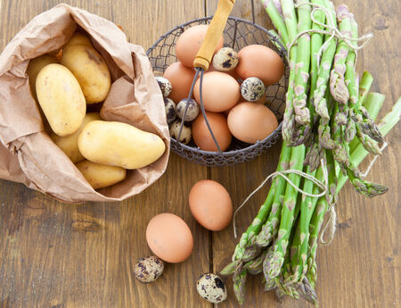 Fresh asparagus, potatoes, and raw eggs in little basket photo
