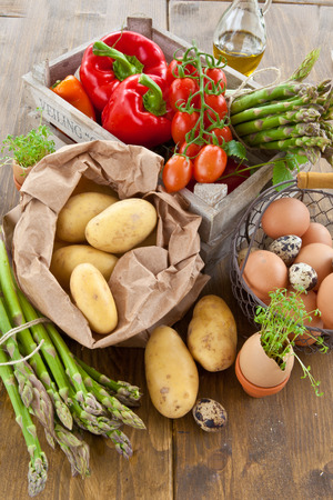 Fresh organic vegetables and eggs in wooden crate photo