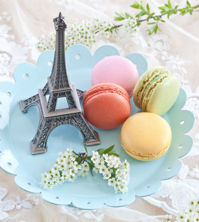 Colorful macaroons on blue plate and a little Eiffeltower photo
