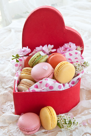 Colorful french macaroons in red heart-shaped box photo