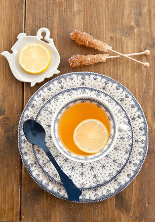 Cup of tea with a slice of lemon on wooden background photo